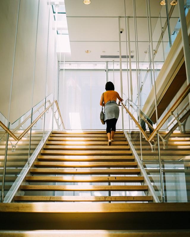žena jde po schodech, kde je skleněné zábradlí.jpg